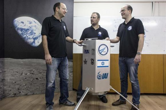 The co-founders of SpaceIL Bash, Damari and Winetraub stand next to their company's spacecraft process prototype near Tel Aviv
