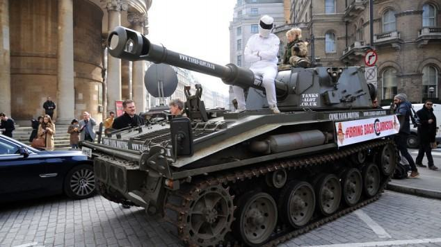 Man dressed (poorly) as The Stig sat on cannon of tank hired by #BringBackClarkson campaign Campaign to reinstate Jeremy Clarkson on Top Gear outside BBC Broadcasting House, London, Britain - 20 Mar 2015  (Rex Features via AP Images)