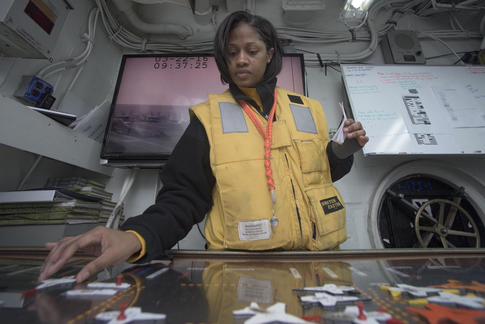 160322-N-KK394-052ATLANTIC OCEAN (March 22, 2016) - Aviation Boatswain's Mate (Handling) 2nd Class Kira Edgehill mans the hangar deck control Ouija board aboard the aircraft carrier USS Dwight D. Eisenhower (CVN 69), the flagship of the Eisenhower Carrier Strike Group. Ike is underway conducting a Composite Training Unit Exercise (COMPTUEX) with the Eisenhower Carrier Strike Group in preparation for a future deployment. (U.S. Navy photo by Mass Communication Specialist 3rd Class Anderson W. Branch/Released)d)