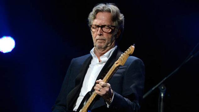 """NEW YORK, NY - DECEMBER 12:  Eric Clapton performs at """"12-12-12"""" a concert benefiting The Robin Hood Relief Fund to aid the victims of Hurricane Sandy presented by Clear Channel Media & Entertainment, The Madison Square Garden Company and The Weinstein Company at Madison Square Garden on December 12, 2012 in New York City.  (Photo by Kevin Mazur/WireImage for Clear Channel)"""