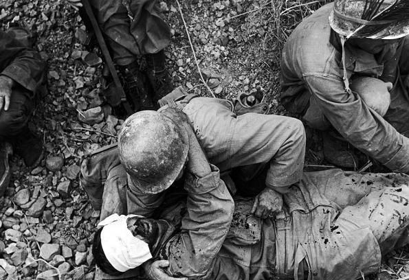 A soldier from the US 7th Army Division comforts a wounded comrade during the fight for Okinawa, Japan, May 1945. (Photo by W. Eugene Smith/Time & Life Pictures/Getty Images)