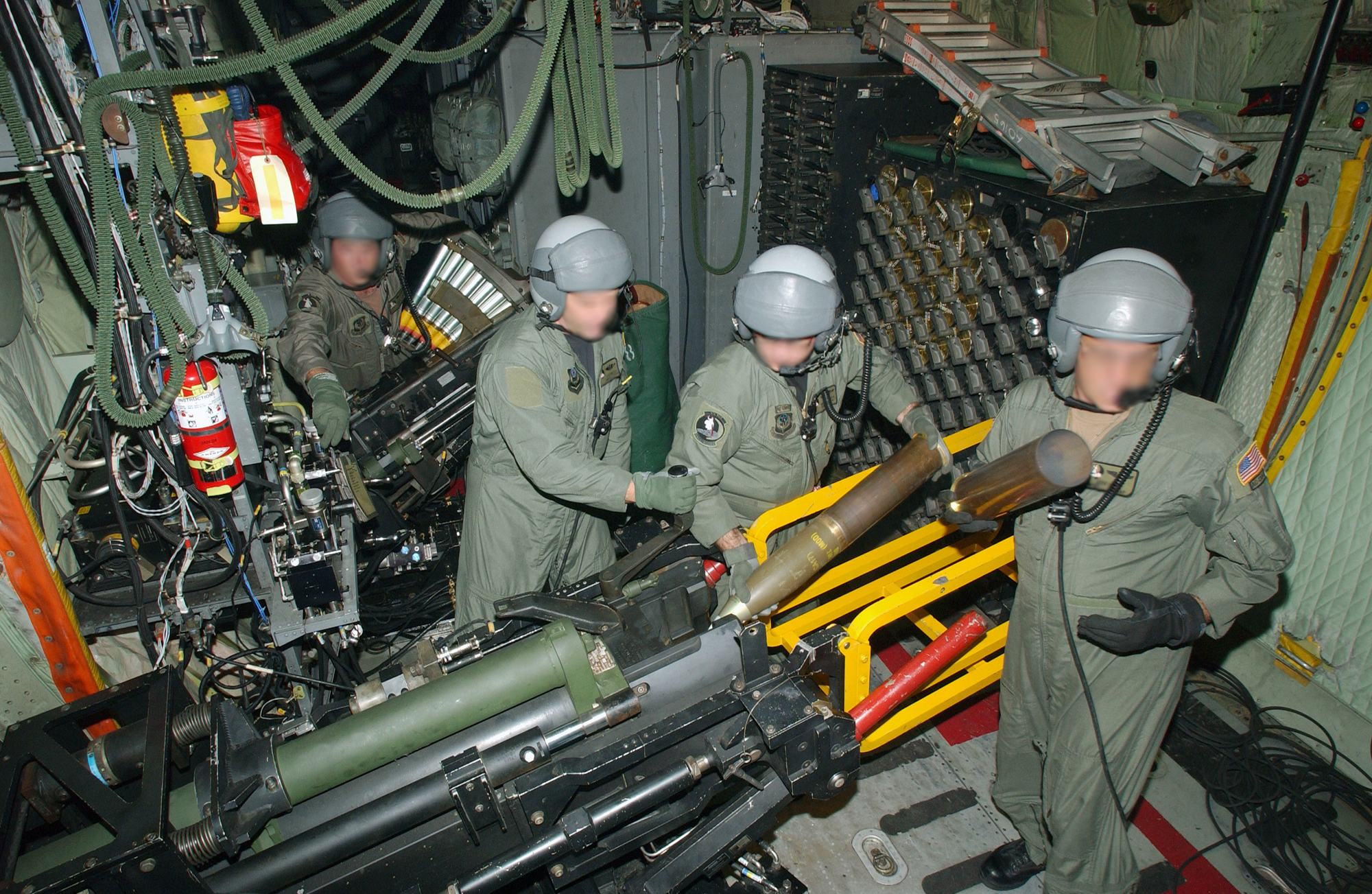 """US Air Force (USAF) aircrew members onboard a USAF AC-130U Hercules """"Spooky"""" Gunship, 4th Special Operations Squadron (SOS), Hurlburt Field (FLD), Florida (FL), load the 40-mm Bofors gun (rear) and 105-mm Howitzer in the cargo compartment during a training mission."""