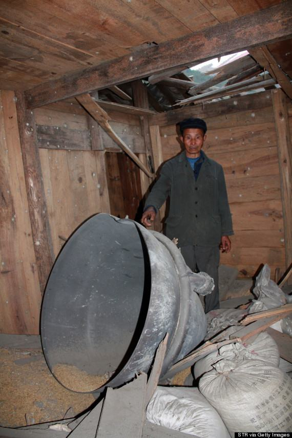 This picture taken on December 2, 2013 shows a man pointing to debris from the rocket carrying China's first moon rover in a house in Suining, central China's Hunan province. The debris plummeted to earth in a village more than a thousand kilometres from the launch site, crashing into two homes, a report said on December 3, 2013. CHINA OUT AFP PHOTO (Photo credit should read STR/AFP/Getty Images)