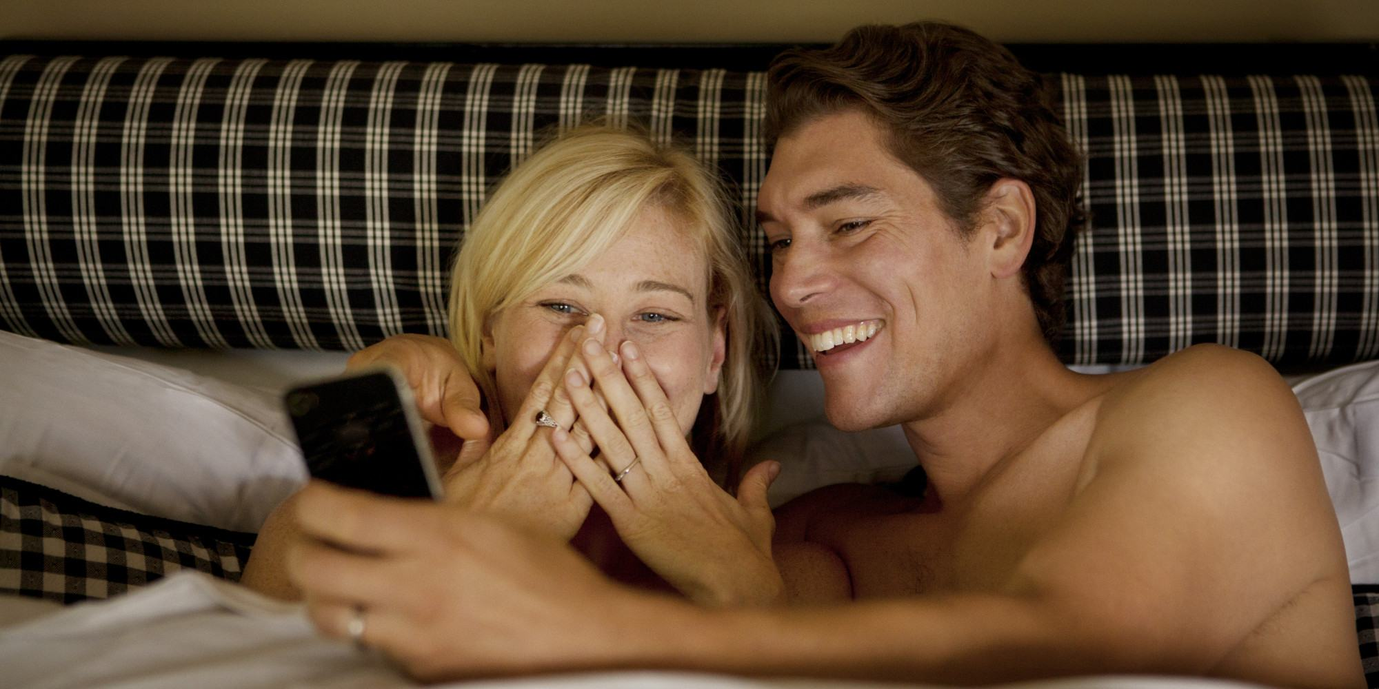 Couple Laughing In Bed With Smart Phone