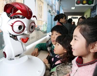 Crianças brincam com robô responsável por R-learning. (Etnews)