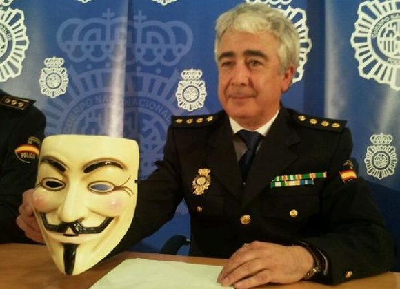 Comissário da Brigada de Investigación Tecnologica exibe máscara usada pelo Anonymous