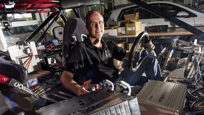 Chris Gerdes dentro de um Buggy cheio de fios e equipamentos eletrônicos. Mas funciona.