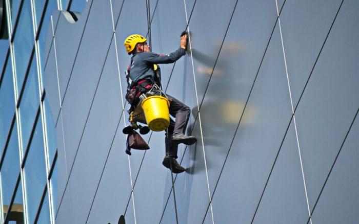 Mircea Lancu / homem limpando janela de edifício / Pexels / como limpar a tela do celular
