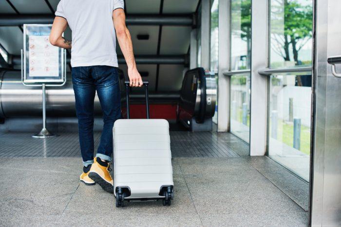 Pessoa com mala de viagem no aeroporto (Foto: rawpixel.com/Pexels)