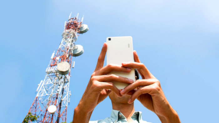 Homem usando celular, com antena ao fundo / o que é 6g