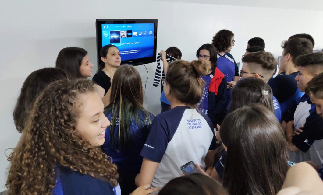 A professora Marili Bassini (ao lado esquerdo da TV) e seus alunos em mais uma aula com games / Crédito: Arquivo pessoal