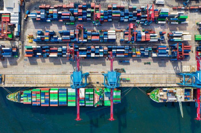 Porto chinês com alguns contêineres bem como um navio sendo carregado