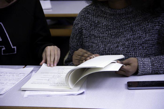 Menina estudando com celular ao lado. Imagem: lovingimages/Pixabay