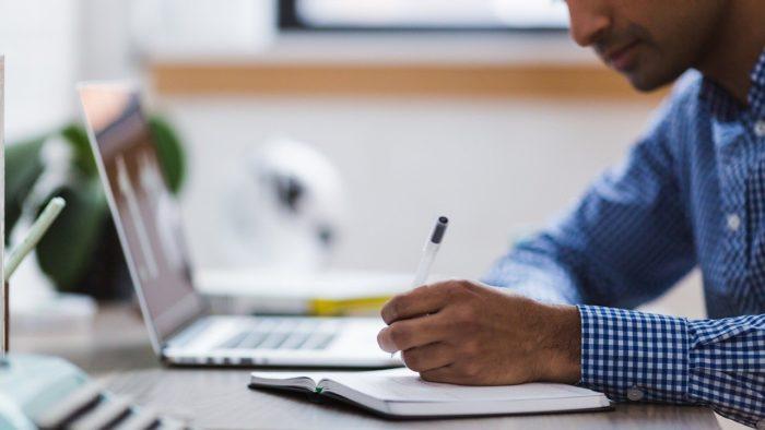 Aluno usando laptop e escrevendo em caderno. Foto: Stocksnap/Pixabay