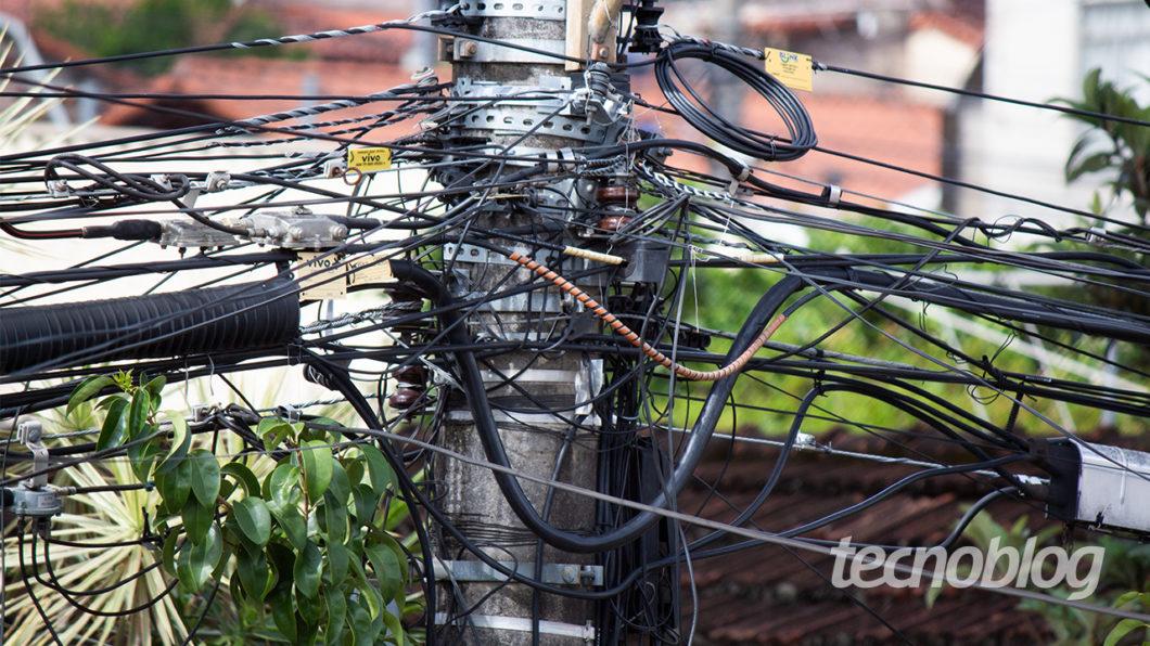 Um monte de cabos de telecomunicações pendurados num poste de energia