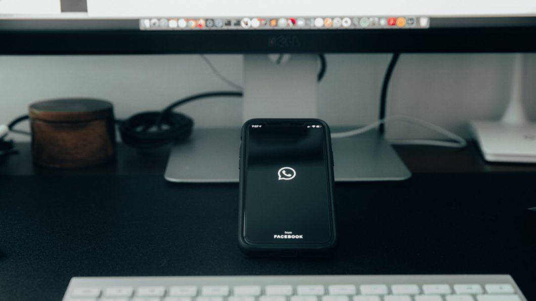 Um celular apoiado na mesa com o aplicativo do WhatsApp aberto e um PC ao fundo (Imagem: Moran/Unsplash)