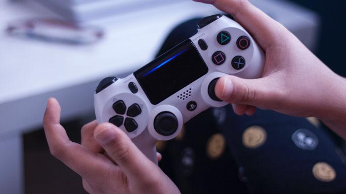 PS4 (ao fundo) e controle DualShock 4 (Imagem: Mélanie THESE/Unsplash)