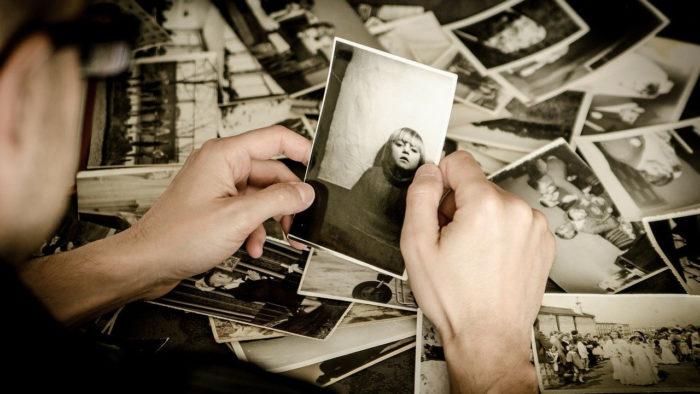 Homem examina coleção de fotos antigas (Imagem: jarmoluk/Pixabay)