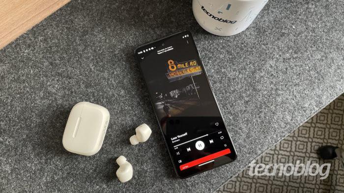 Celular com fone Bluetooth ao lado (Imagem: Darlan Helder/Tecnoblog)
