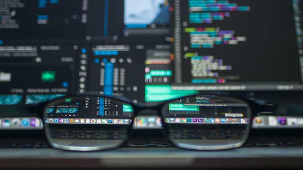 Óculos na mesa diante de uma tela com códigos