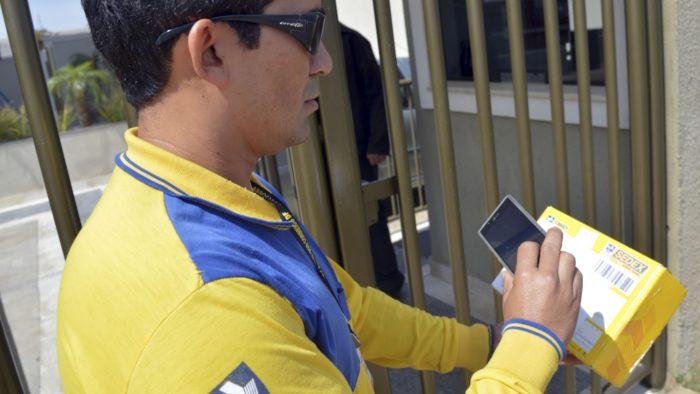Carteiro faz entrega usando celular dos Correios (Imagem: Divulgação)