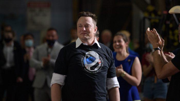 Elon Musk cercado por pessoas e sendo aplaudido