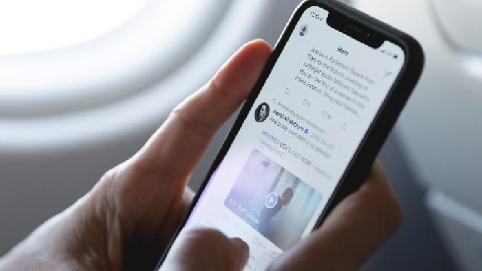 pessoa segurando um celular preto com uma timeline do twitter aberta