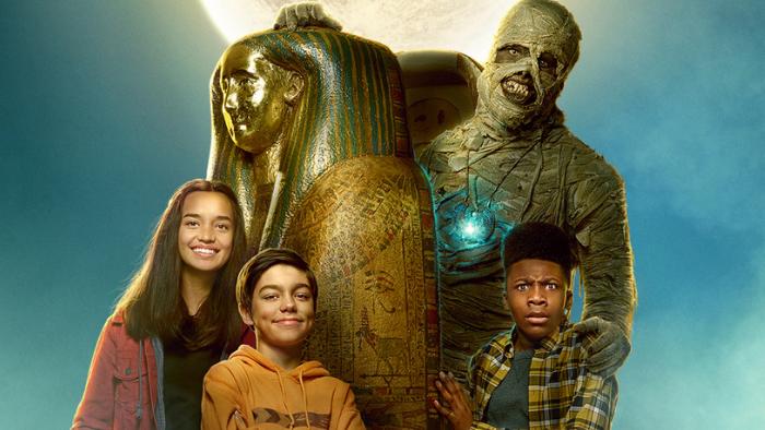 a girl in a red shirt, a boy in an orange shirt, a boy in a plaid shirt, and a mummy behind them all.