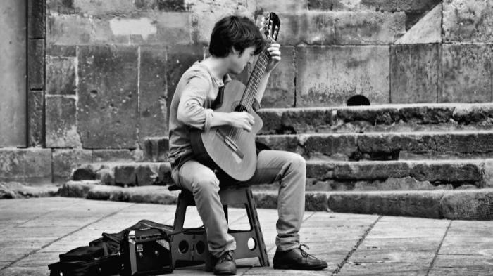 Homem compondo música no violão (Imagem: Zibik/Unsplash)