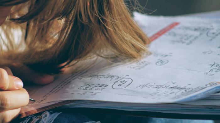 Estudante debruçada sobre exercícios de matemática (Imagem: Joshua Hoehne/Unsplash)