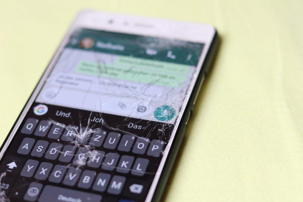 Imagem de um celular quebrado em cima de uma mesa com o WhatsApp aberto