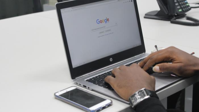 pessoa com a mão no computador com a tela no google e um celular do lado